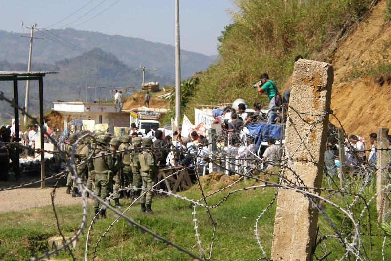 À travers des barbelés, on voit quelques soldats très armés au côté d'une foule d'hommes et de femmes mexicains. Plusieurs portent des chemises blanches. On voit aussi un caméraman sympathisant sur un camion.