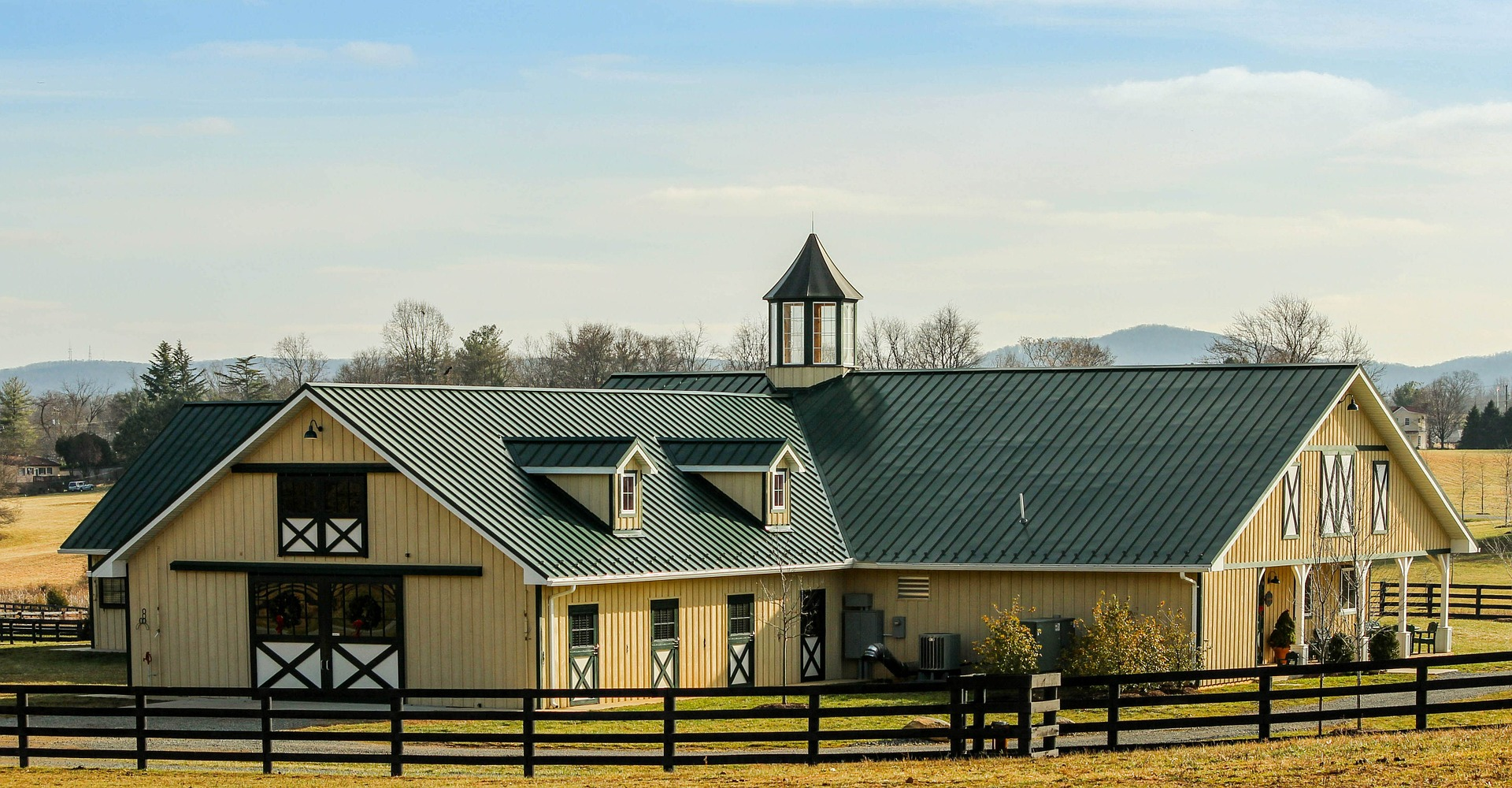 expensive-looking tan horse barn with green roof