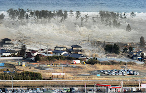 A massive tsunami engulfs a residential area after a powerful earthquake in Natori, Miyagi Prefecture, northeastern Japan on March 11.