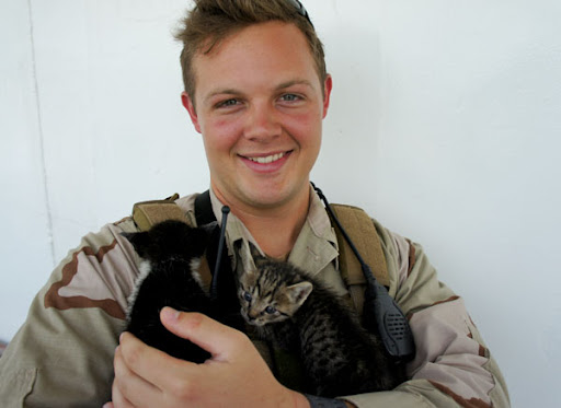 US navy sailor holds 2 kittens rescued on board