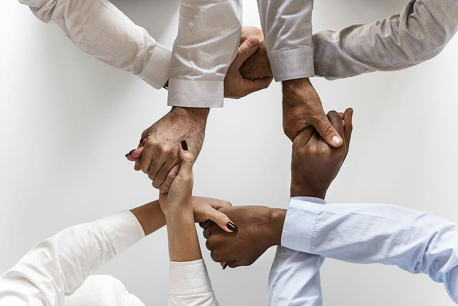 Four people join hands to demonstrate their support for a startup they are funding