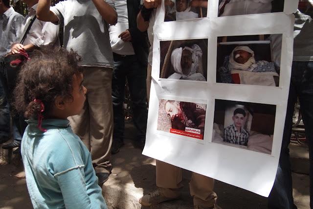 فتاه صغيرة تنظر الى صور قتلى وجرحى في سوريا
