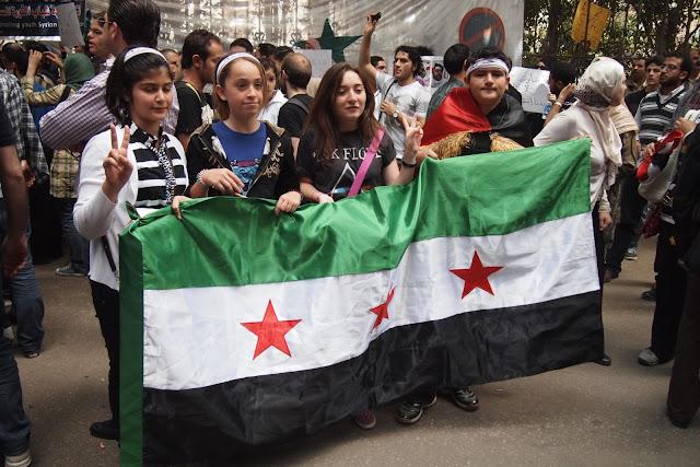 مجموعة من الأطفال السوريون يرفعون علمهم أمام السفارة السورية بالقاهرة