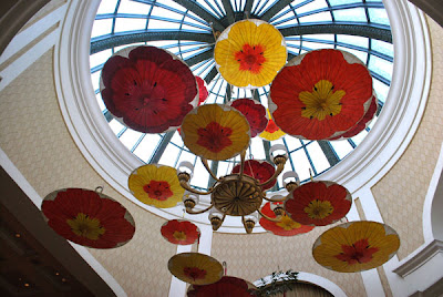 Handpainted umbrellas with large colorful poppies hang upside down from wires in an artistic show, under the glass ceiling of the Bellagio Hotel and Casino, Las Vegas, NV.