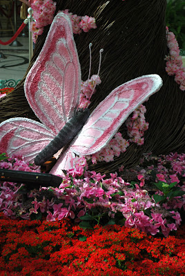 This is a photo of a large pink butterfly resting against a handcrafted tree inside the Conservatory of the Bellagio Hotel and Casino, Las Vegas, NV.