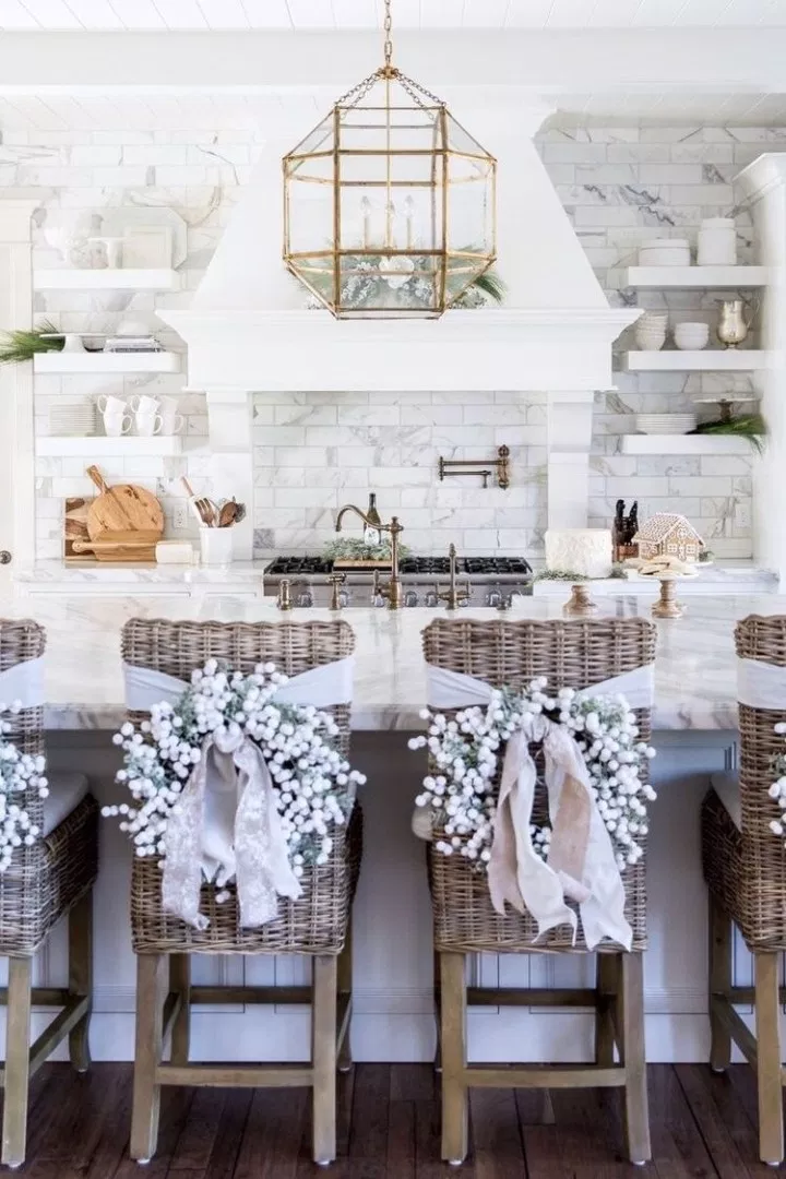 modern white kitchen with large center island. the seating around the island features chic white christmas wreaths tied with ribbon around the back of the chairs