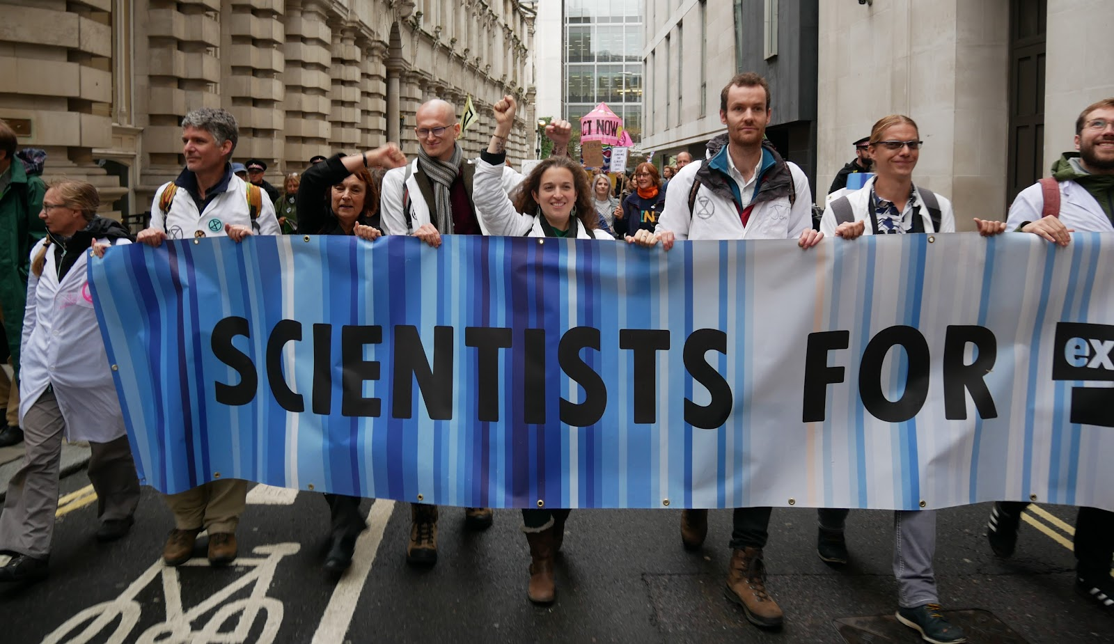 Scientists for XR wearing lab coats, and marching with an XR banner.