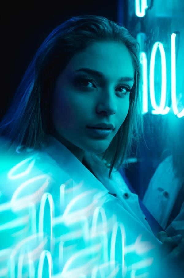 mulher branca ao lado de um letreiro azul no estilo neon