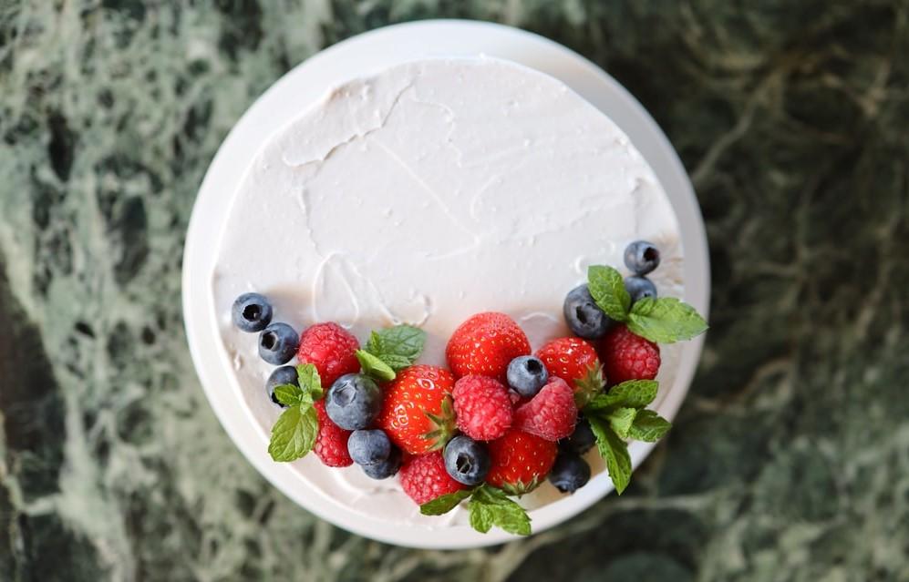 Bolo vegano em formato redondo, com cobertura de chantilly branco. Em um dos lados superiores, está decorado com morango, mirtilo, fambroesa e folhas de hortelã.