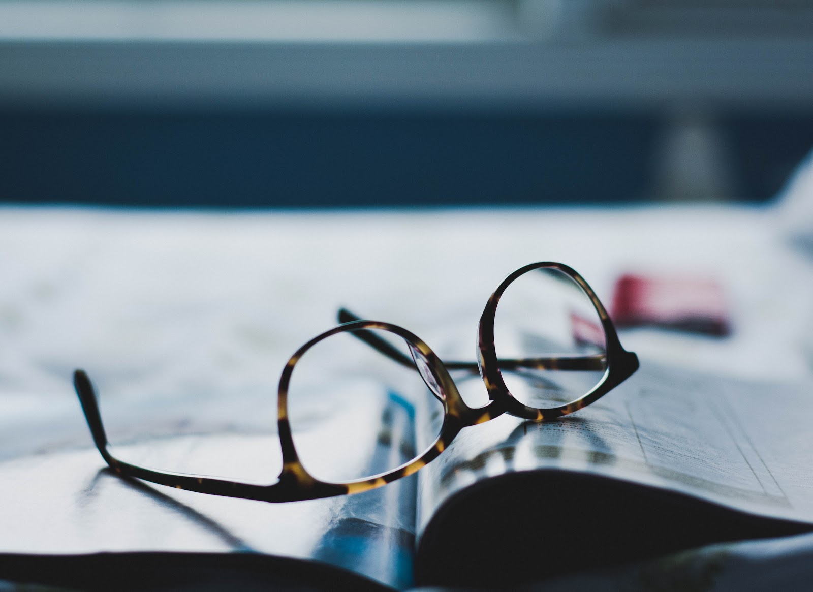 Pair of glasses on an open magazine