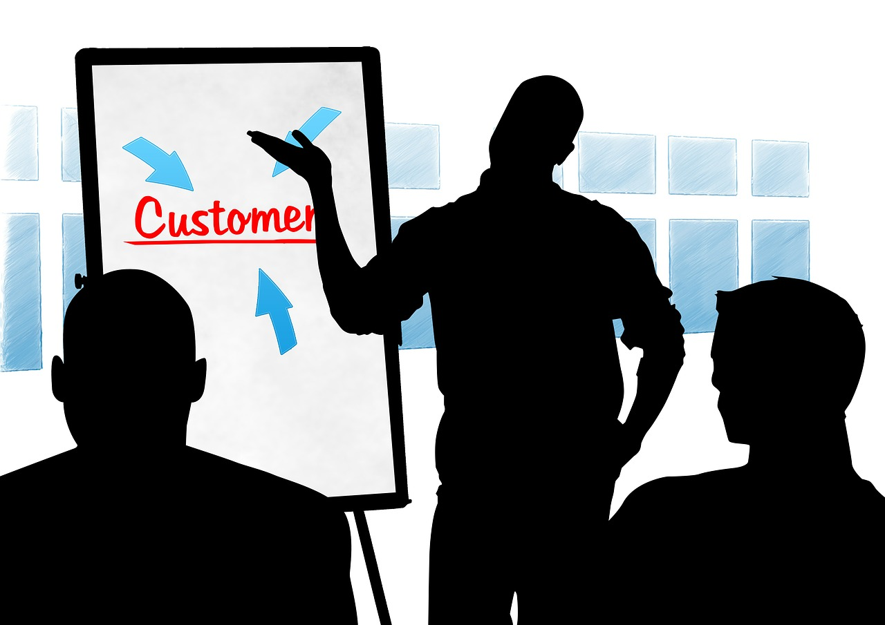 """A man standing in front of a board with the word """"Customer"""""""