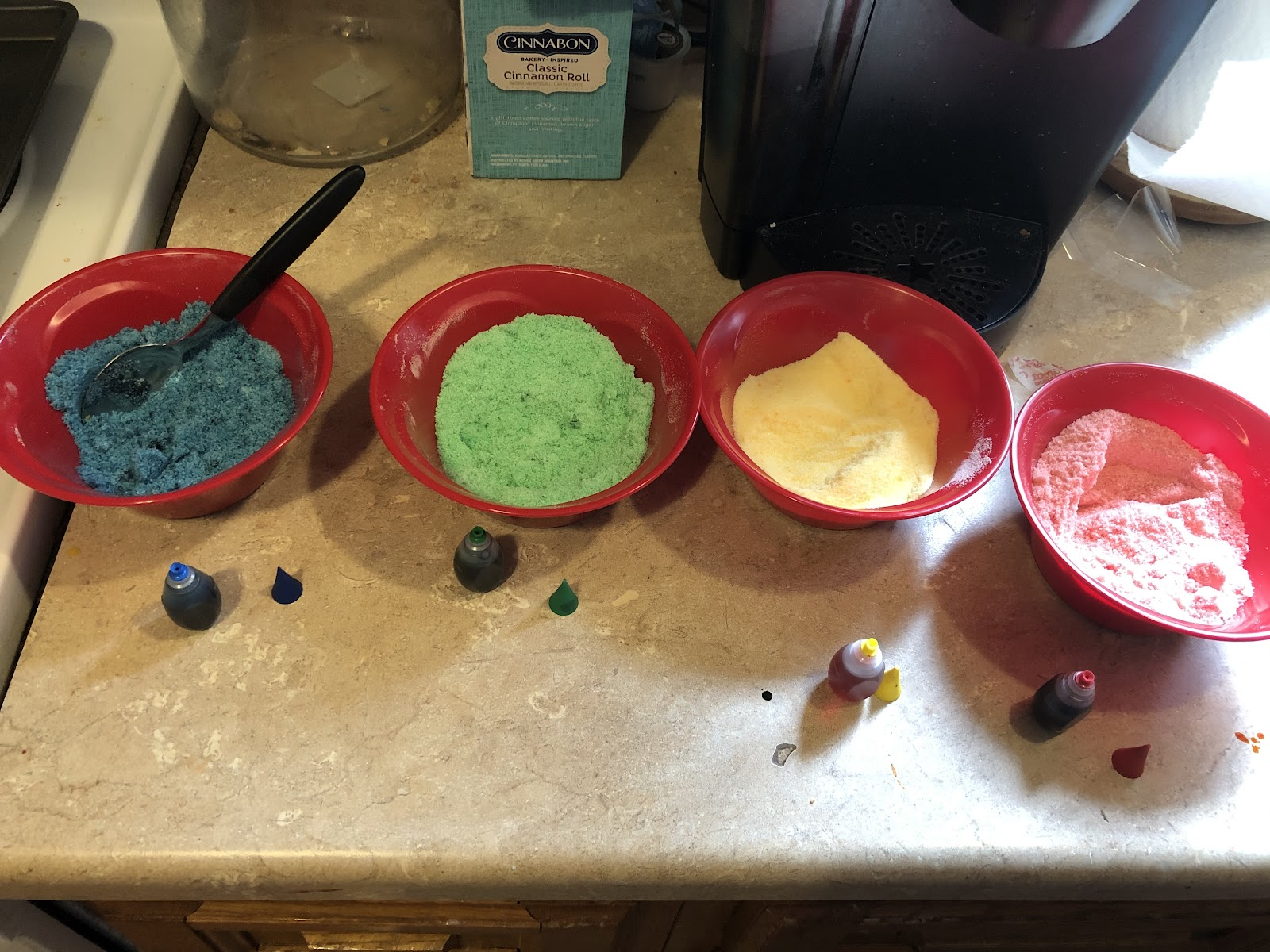 Four bowls with colored sugar in them.