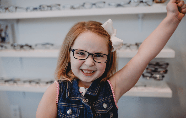 A little girl with red hair celebrating her first pair of glasses with her fist in the air from excitement.
