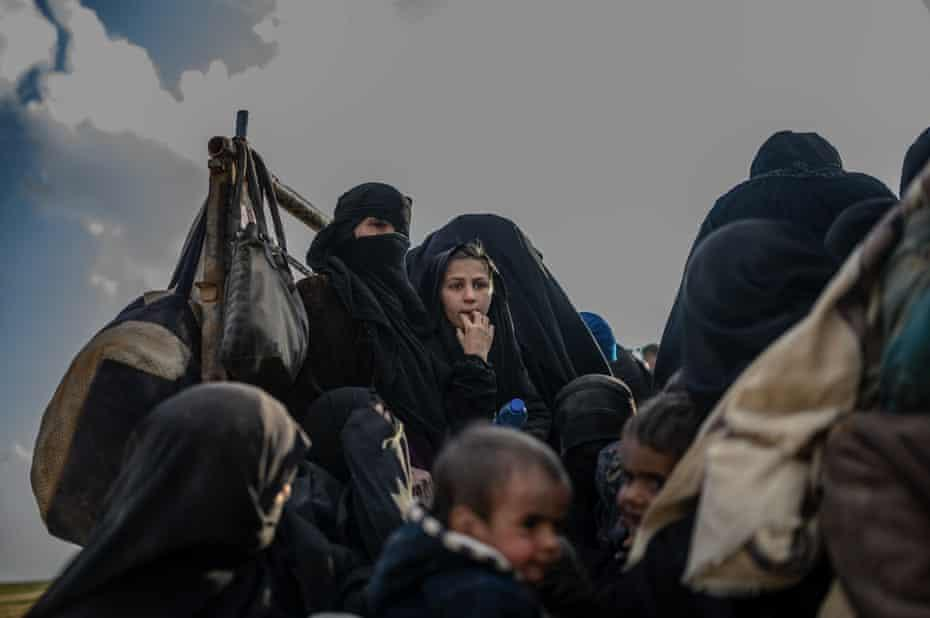 Families who fled Isis's last holdout of Baghuz sit in a truck in Deir Ezzor. There are plans for a second commune in the Arab province.