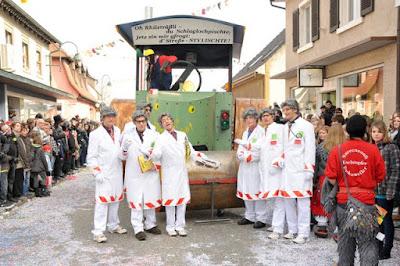 Baumann, Sänger und Co. rücken den Schlaglöchern auf der Rheinstraße mit einer gewichtigen Dampfwalze zu Leibe.