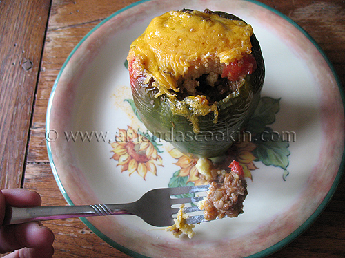 A close up photo of a forkful of chili and cornbread stuffed pepper with the whole stuffed pepper in the background.