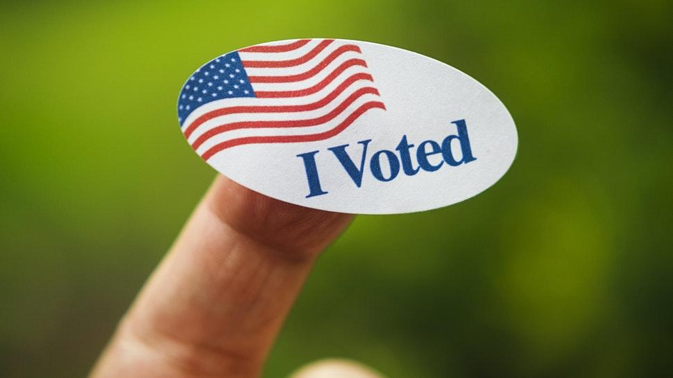 Close-up of I voted sticker on finger - stock photo