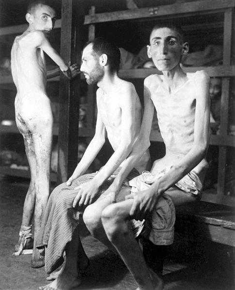 Three corpse-thin men in the barracks at Buchenwald.
