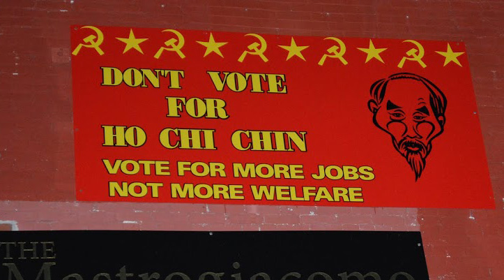 "Joe Dunne's ""Don't Vote for Ho Chi Chin: Vote for more jobs not more welfare"" poster with stars and hammer-and-sickle symbols. It also includes a caricature of Ho Chi Minh."