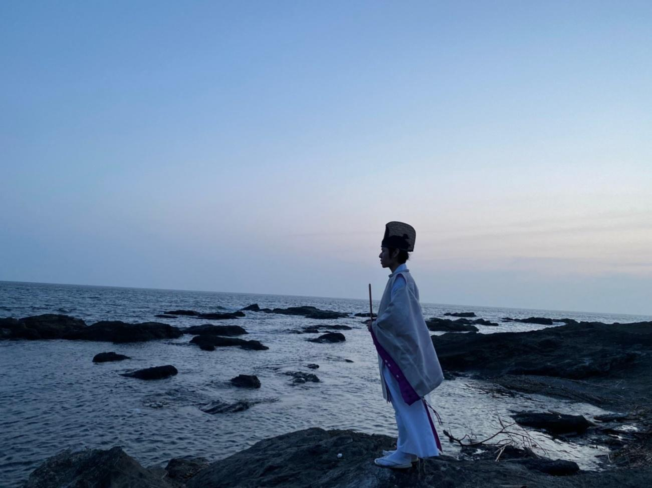 Soushi dressed as a shinto priest if facing the sea at sunset