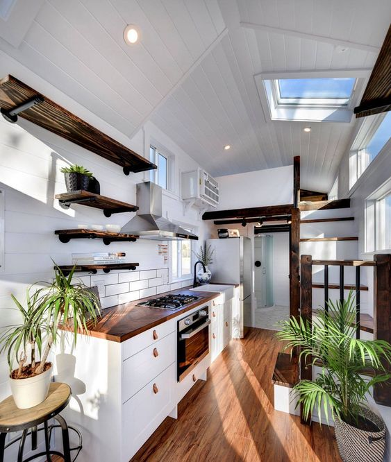 bright coastal tiny home kitchen with open shelving, white flat panel kitchen cabinets, wood floors, white painted walls and potted plant decor. coastal tiny house decor - hgtv tiny homes - tiny house kitchen ideas