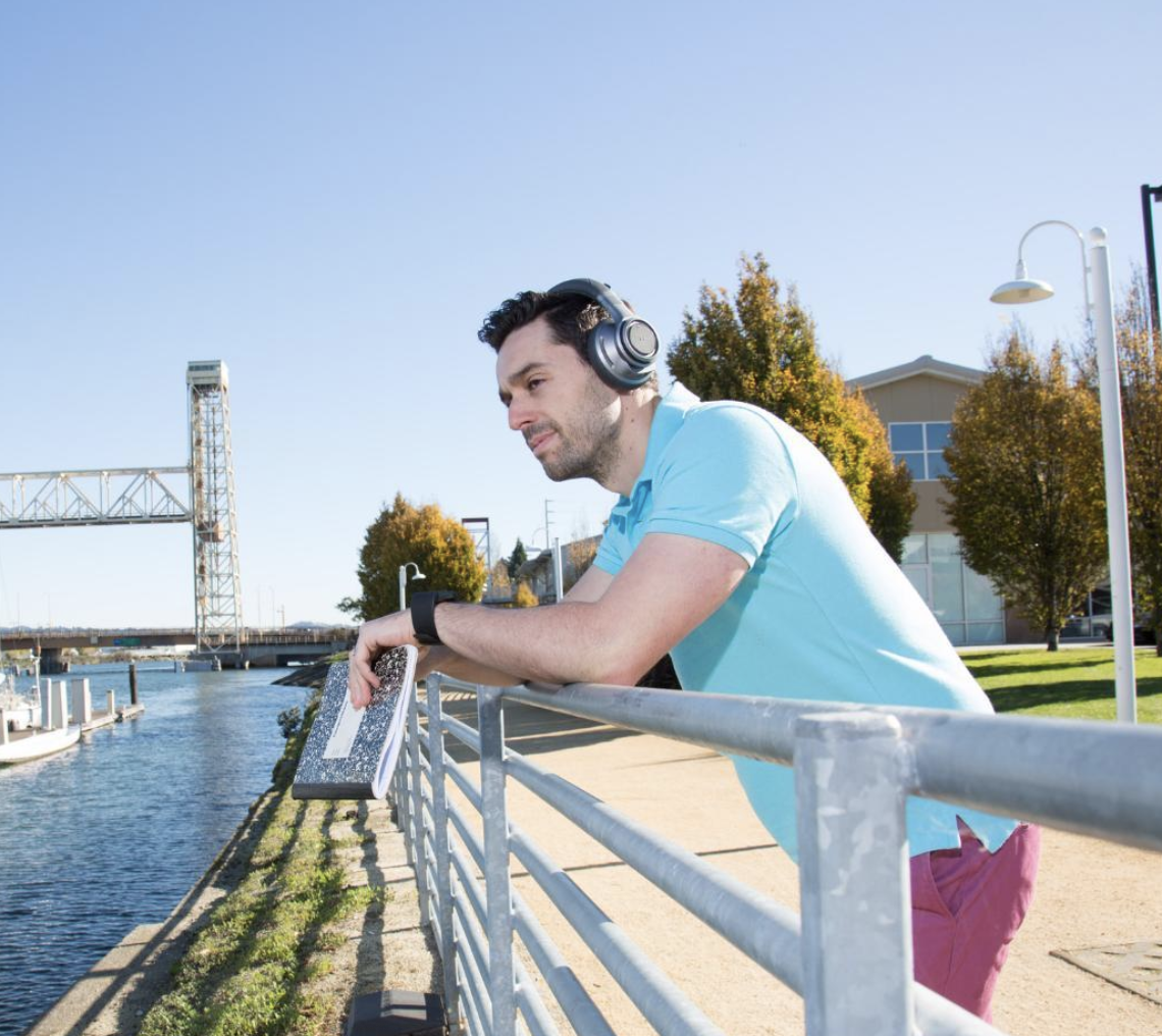 Jacob Morgan   Wearing headphones leaning on rail overlooking the river