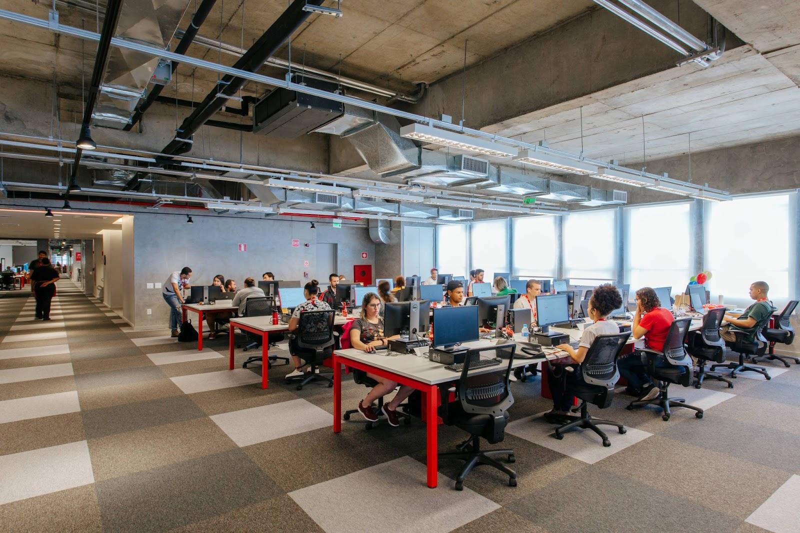 Colaboradores trabalhando em um ambiente moderno e confortável, que auxilia na qualidade de vida no trabalho