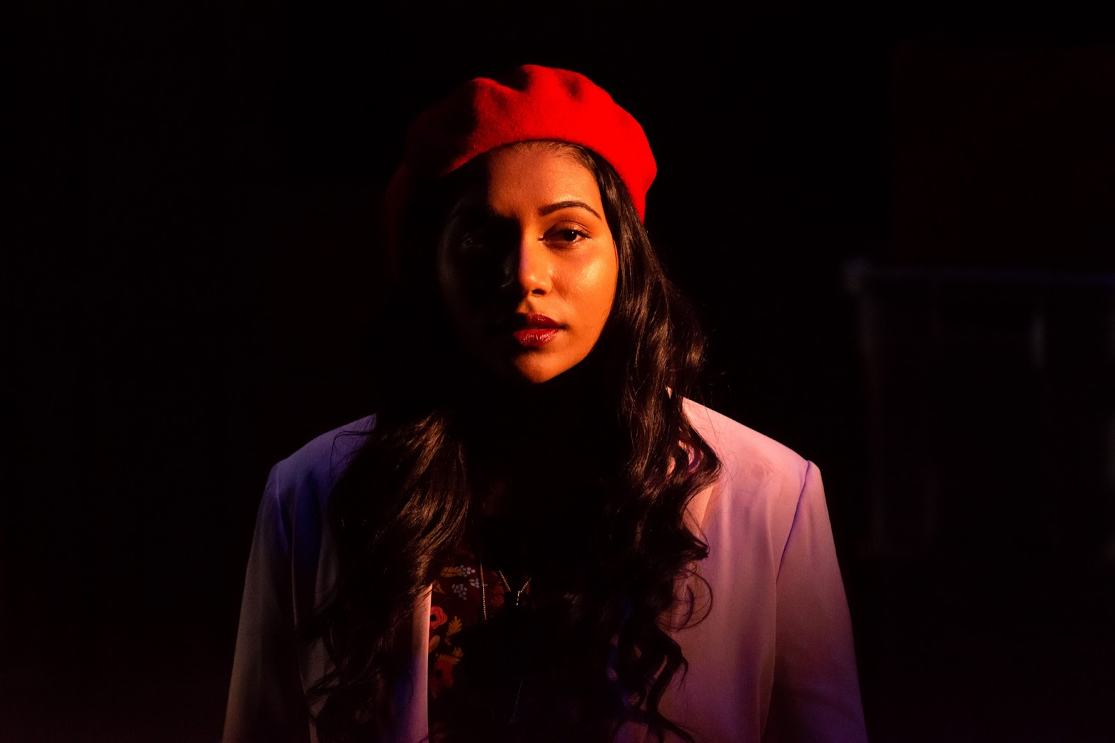 Caitlyn Hooper, with long dark hair, stands against a pitch black background while wearing a red cap and a light colored jacket.