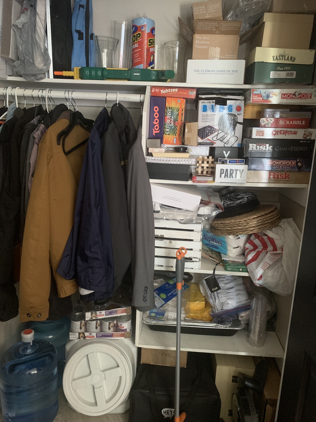 hall closet cluttered with jackets, board games, cleaning supplies, catering supplies, shipping boxes, etc.