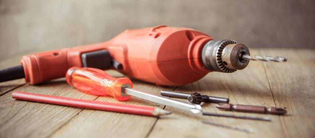 Na imagem, uma furadeira na cor laranja com várias outras ferramentas, lápis, chave phillips, chave de aperto e bits. | Guia completo das Furadeiras.
