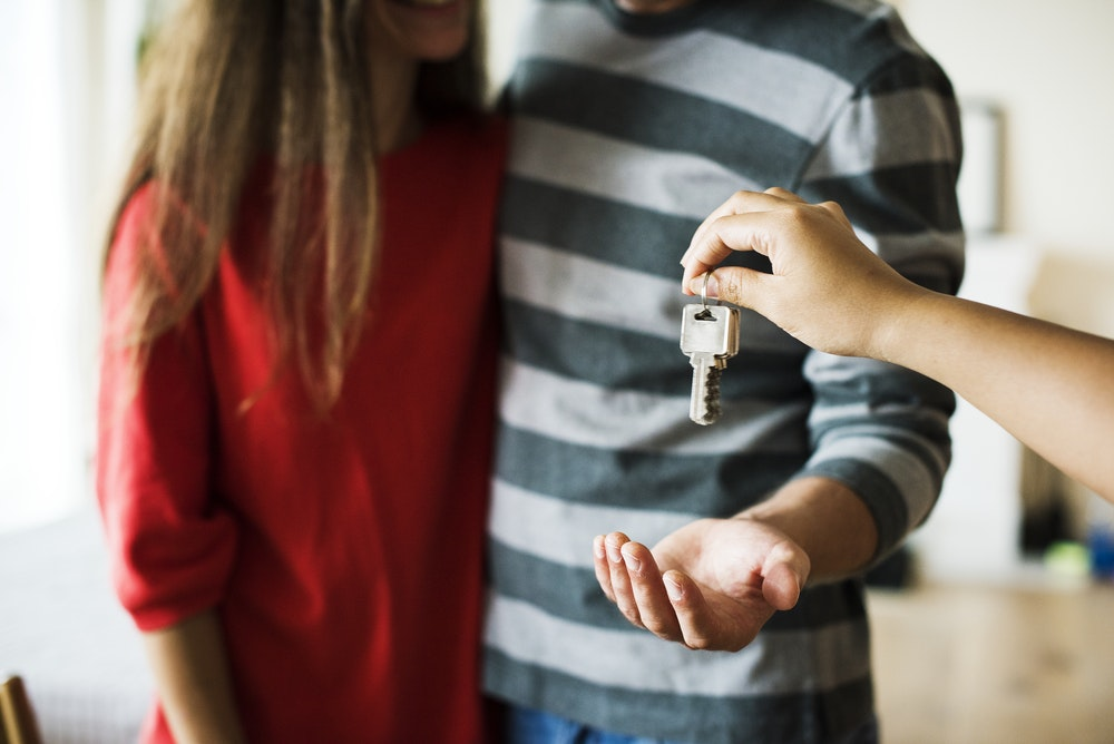 person hanging keys to man's hand standing next to girl