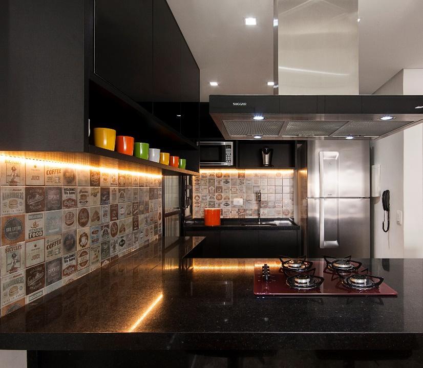 Cozinha com azulejos personalizados com imagens de alimentos, bancada preta de mármore, armários preto e coifa.