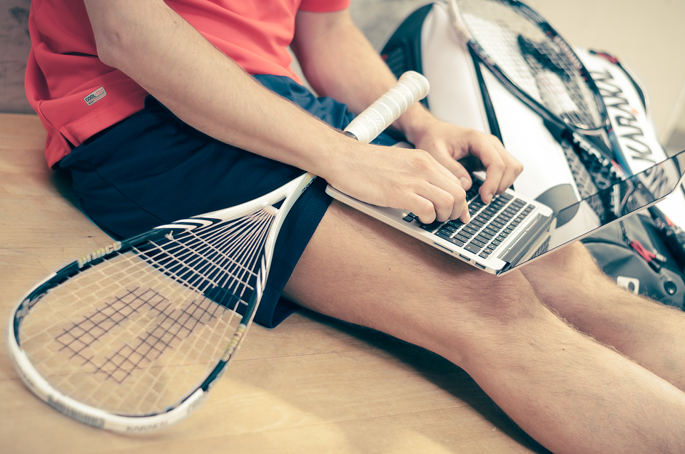 bottom half of man with tennis racket on lap