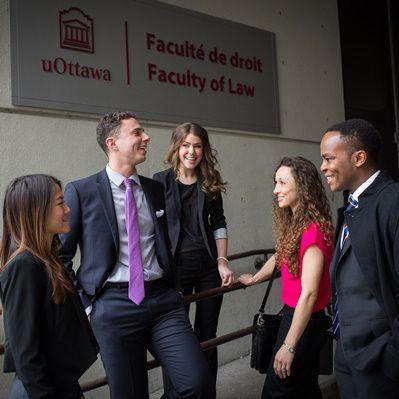 A group of people standing in front of the Faculty of Law