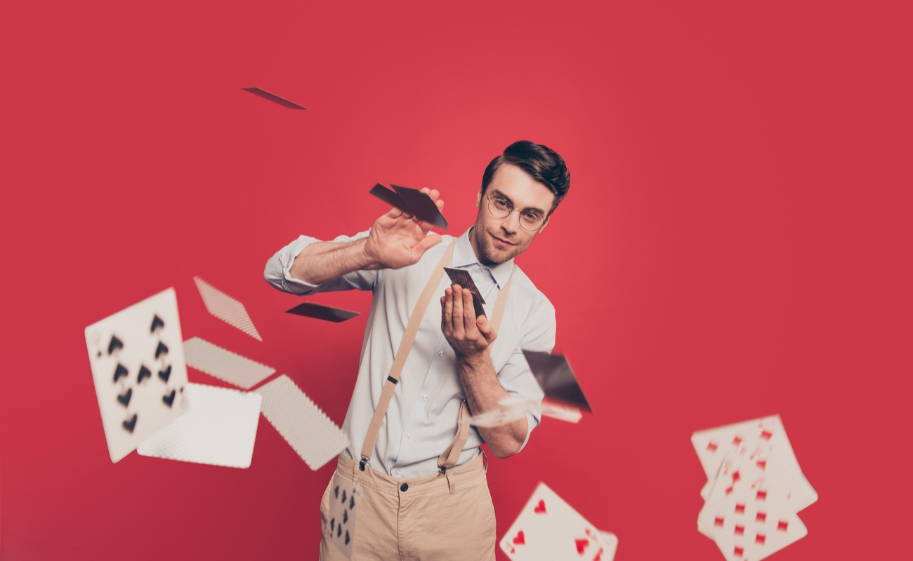 gambler in casual outfit with glasses throwing cards toward the camera against a red background