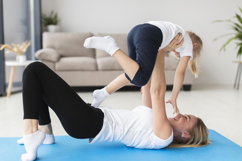 Mãe fazendo exercício com a filha no chão