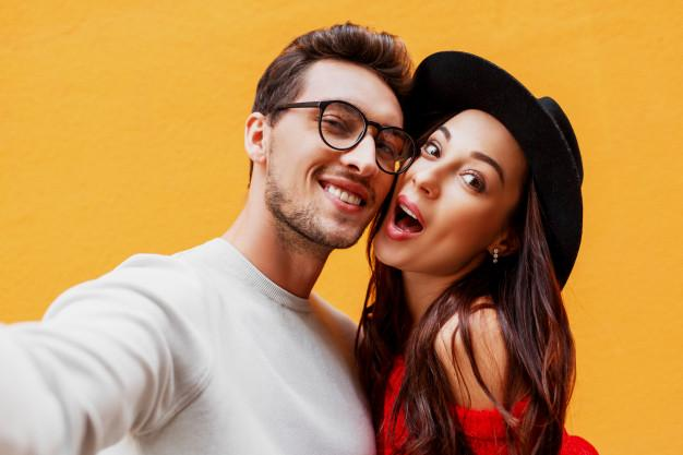 Happy girl with her boyfriend making self portrait by mobile phone. yellow wall. wearing red knitted sweater. new year party mood. Free Photo