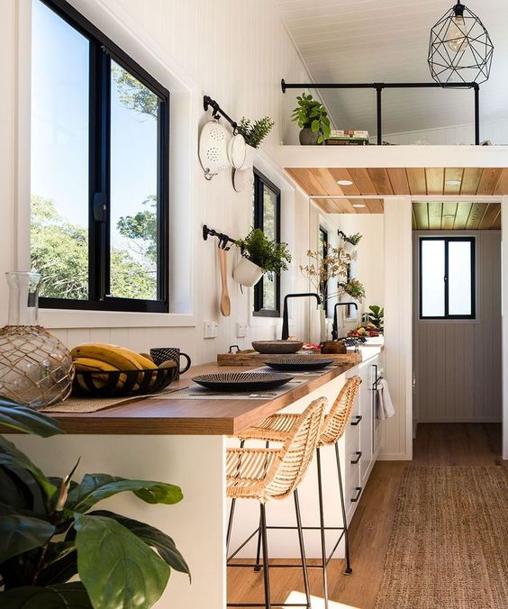 tropical tiny house design with seating area in kitchen, wood floors, white shaker cabinets, large framed window, industrial accents. tiny house kitchen - hgtv tiny homes - white tiny house kitchen ideas