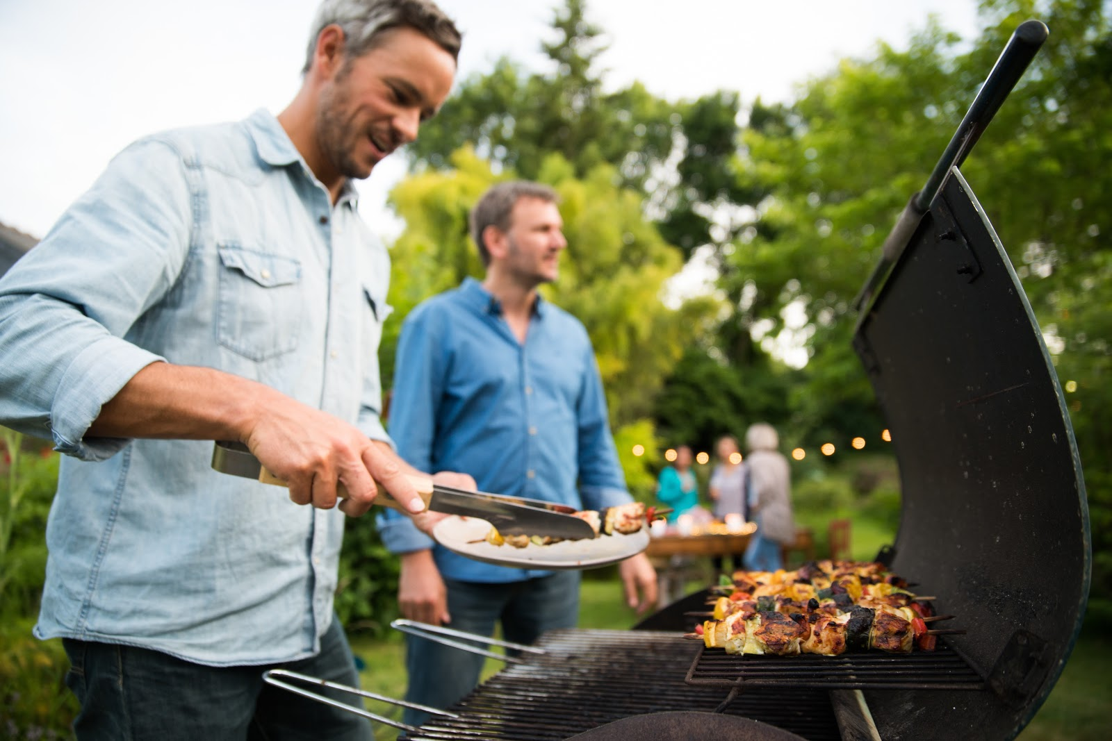 People at a backyard party enjoying grilled food