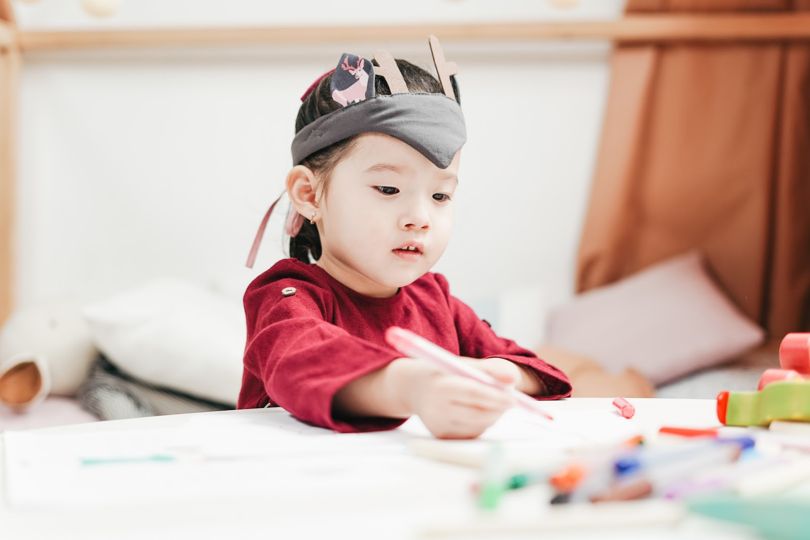 A preschool-aged student is seated at a table with markers, working on a project.