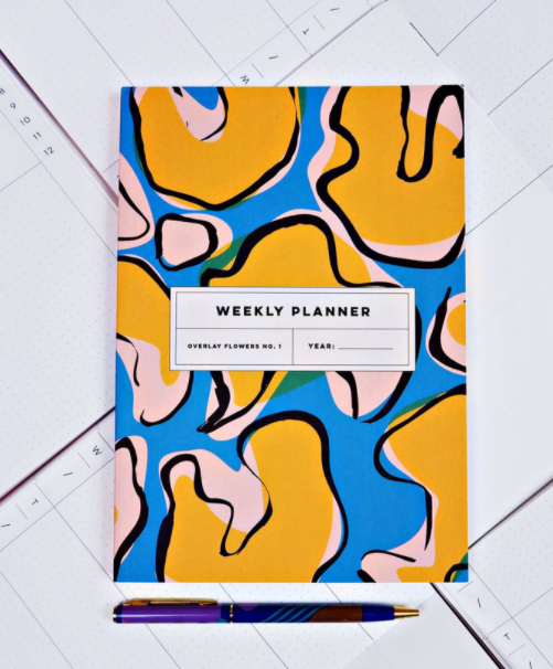 Bright abstract cover of weekly planner flatlay on music paper background