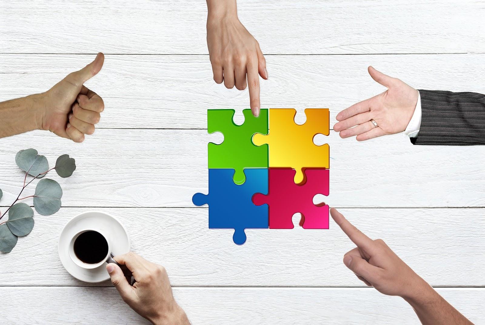 Ręce różnych ludzi układające puzzle.