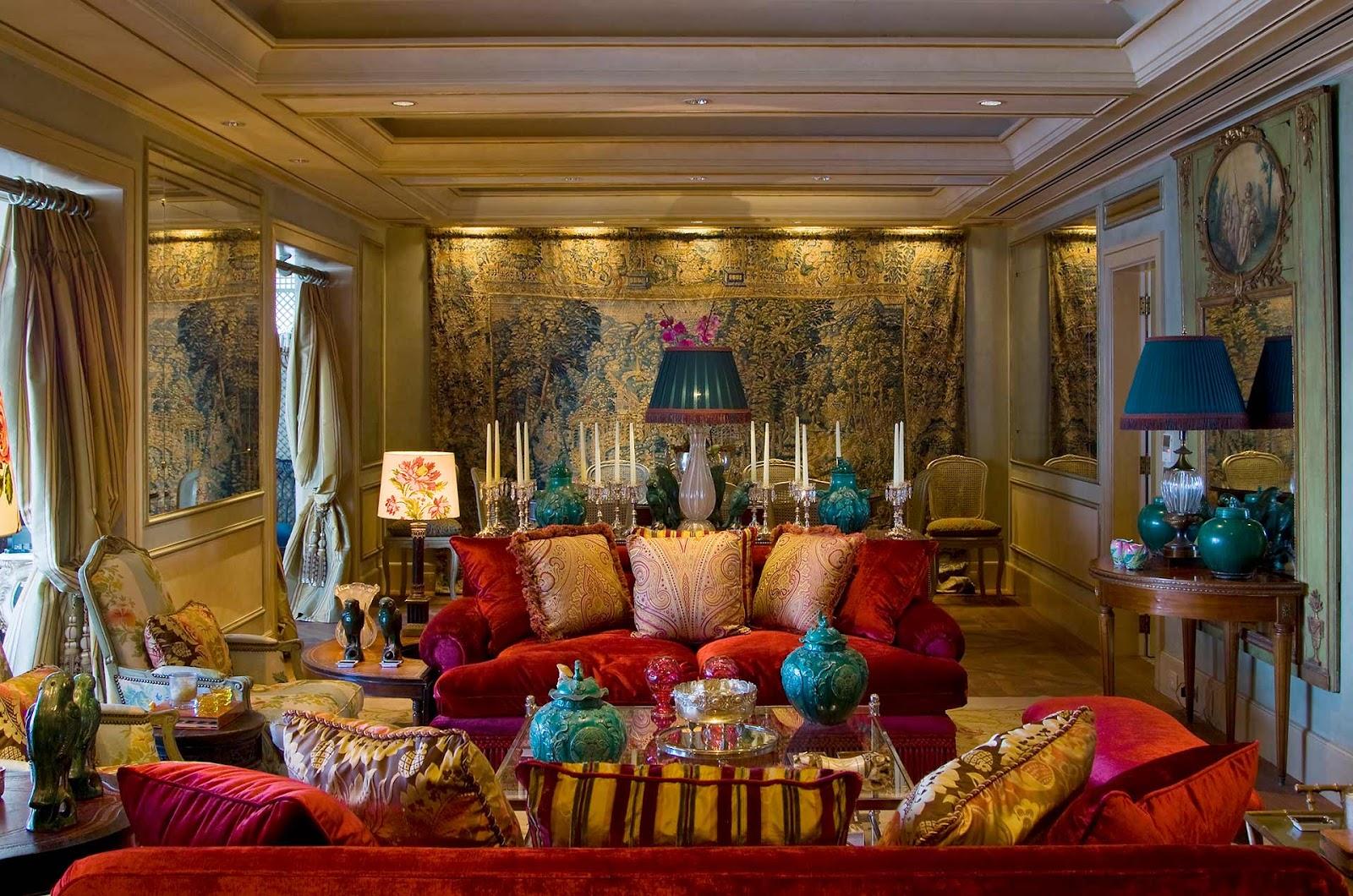 Sala com sofás vermelhos, almofadas coloridas, abajur azul, velas e papel de parede estampado.