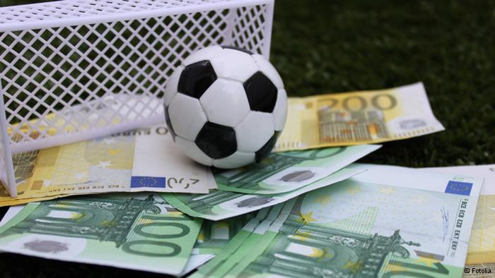 A football ball on a pile of money  Description automatically generated with medium confidence
