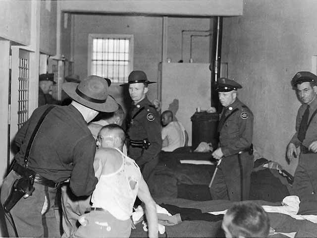 Guards handling Japanese American prisoners inside the Tule Lake stockade. A guard is pulling a man in a torn undershirt off his cot by the arm while three more guards approach. In the background are cell doors and other prisoners sitting on cots.