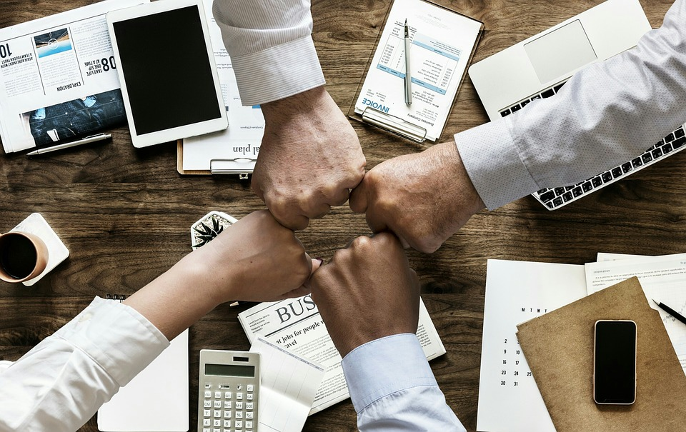 Four people touching fists above a desk