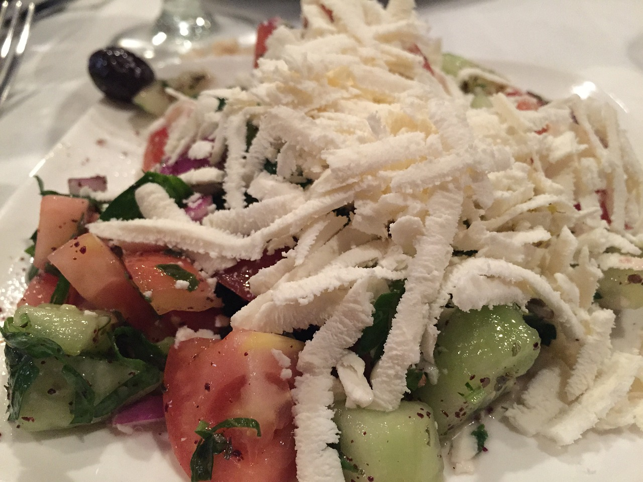 greek salad with heavy layer of shredded feta over cucumbers, tomatoes, and onions