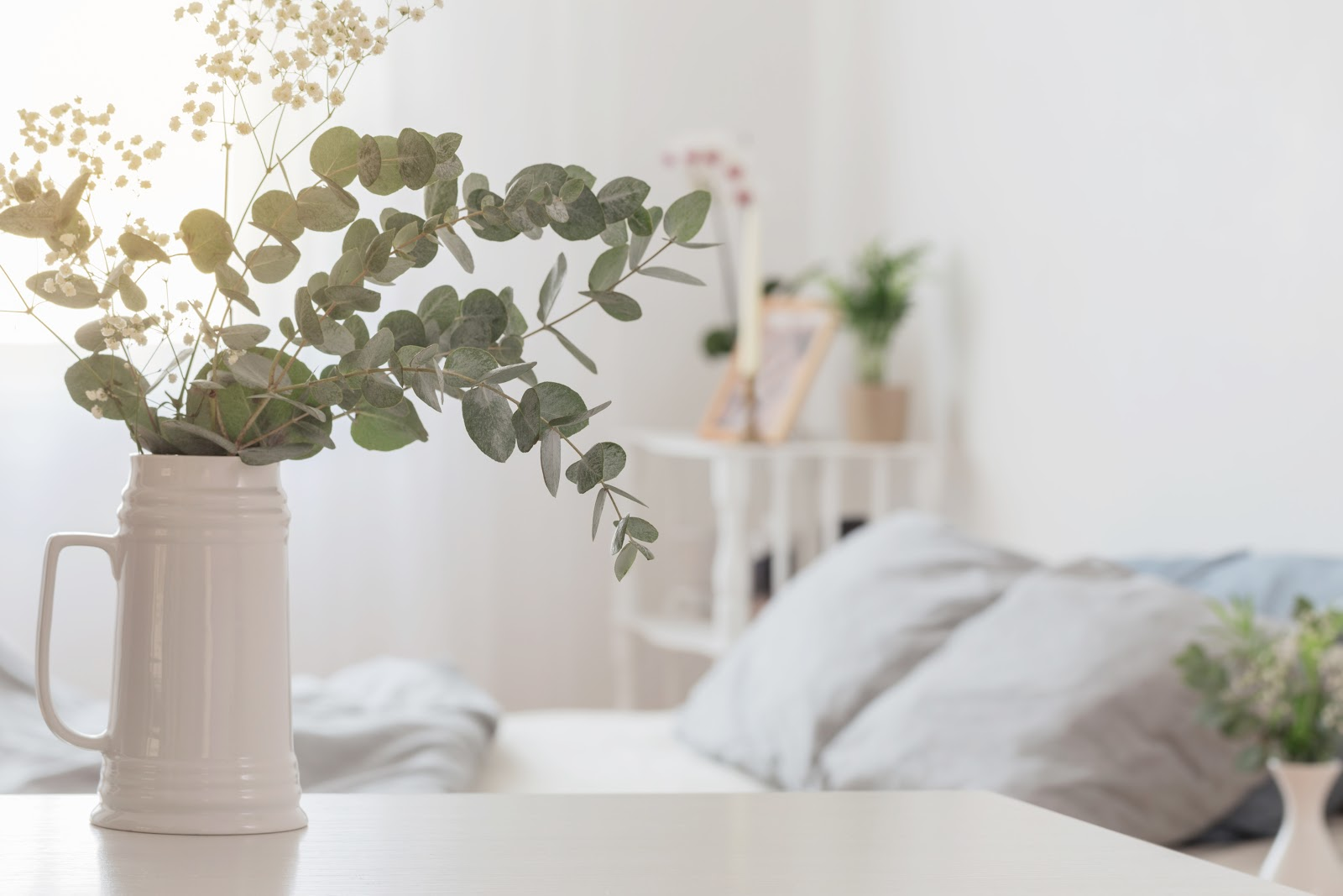 Eucalyptus and gypsophila flowers in a jug in white bedroom.