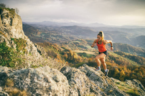 Young woman running on mountain Action photo of athlete woman trail runner running and climbing over mountain cliff. Extreme terrain and beautiful light before sunset after rain. a lady doing vigorous exercise stock pictures, royalty-free photos & images