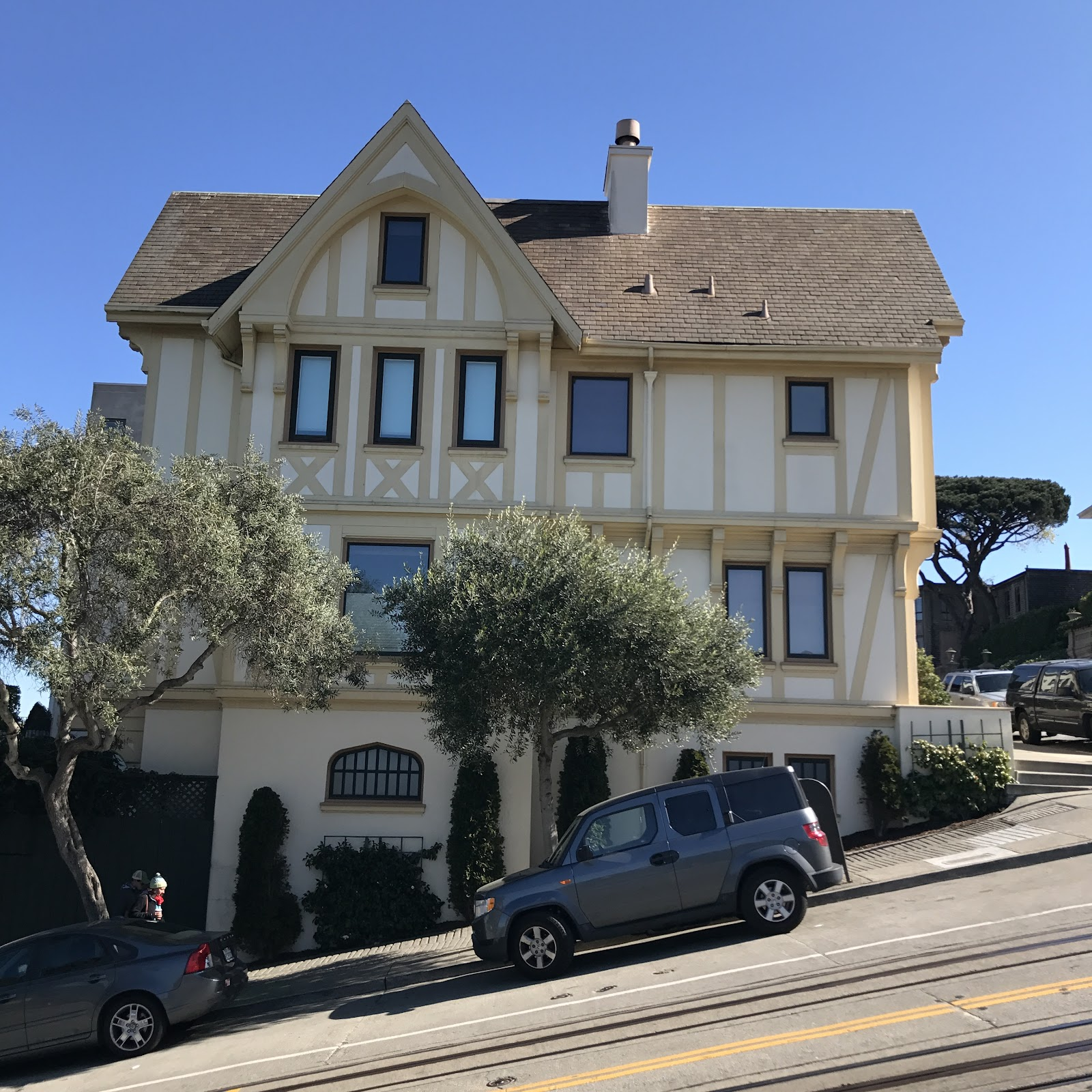 san francisco yellow 3 story home on a crooked street with two cars in the front and iconic tram route